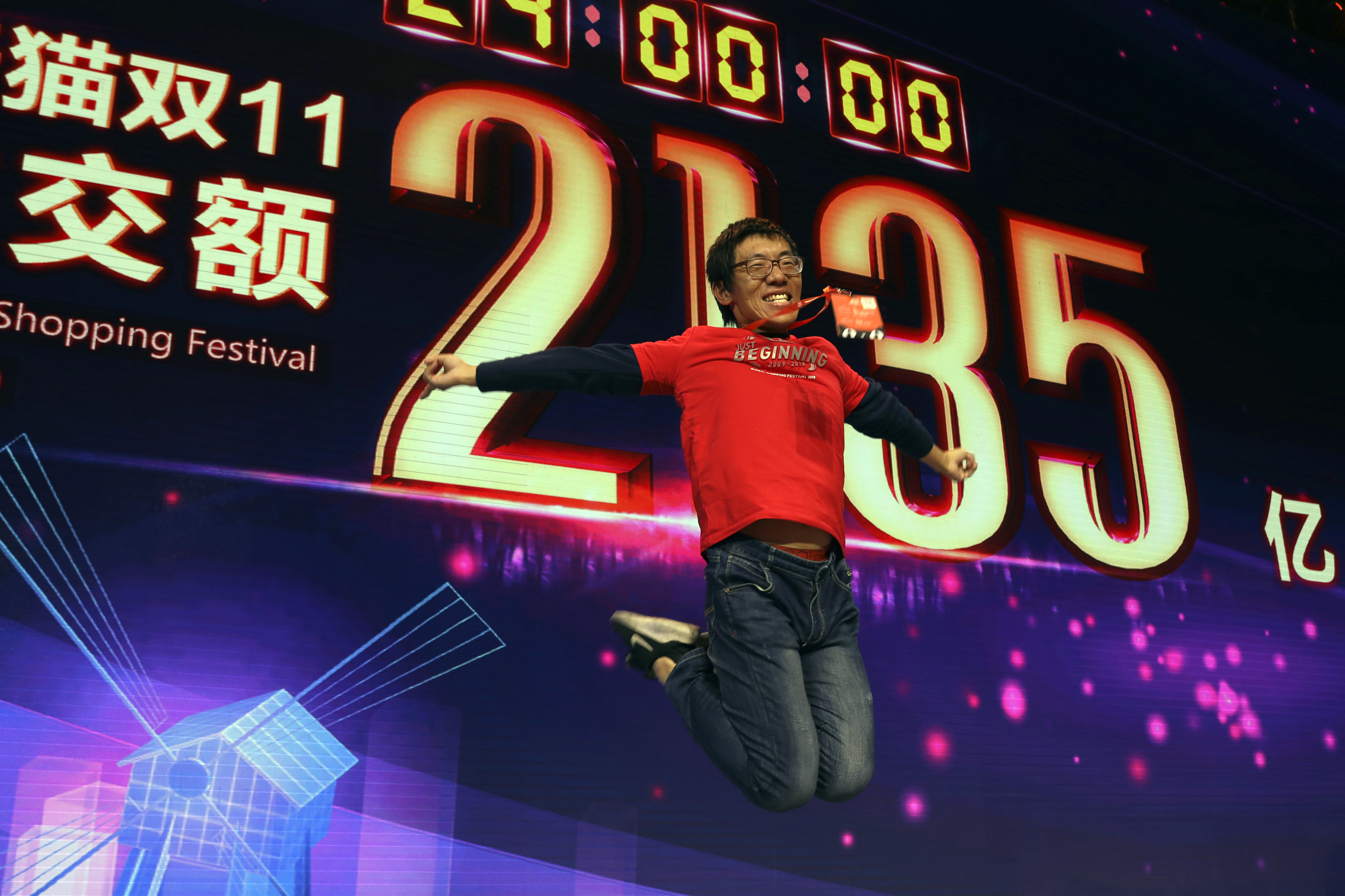 A staff member jumps for a photo to celebrate after Alibaba's 11.11 Global Shopping Festival also known as Singles Day sets a new record