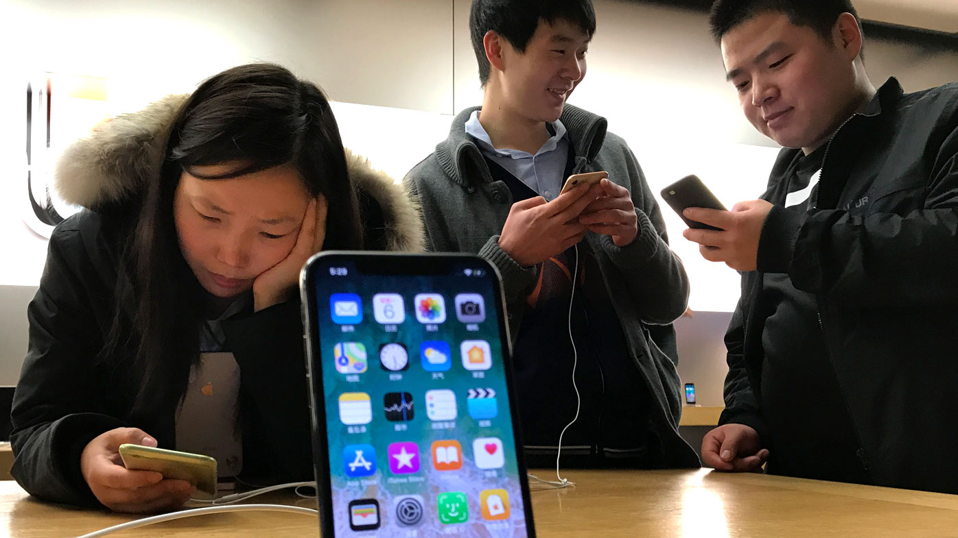 Shoppers check out the iPhone X at an Apple store in Beijing, China
