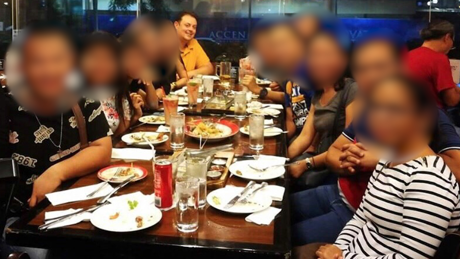 Michael James (back, left) having dinner, believed to be in the Philippines.