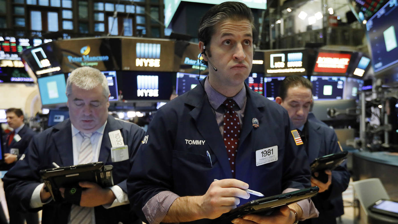 Thomas Donato, center, works with fellow traders on the floor of the New York Stock Exchange.