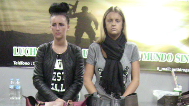 Michaella McCollum Connolly, of Ireland, left, and Melissa Reid, of Britain, stand behind their luggage after being detained at the airport in Lima, Peru. (AAP)