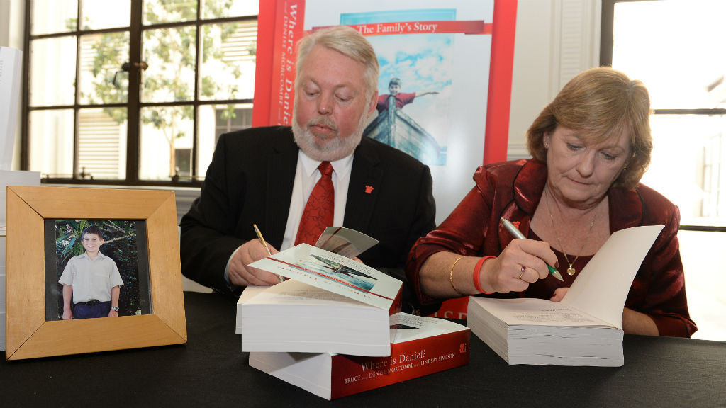 Bruce and Denise Morcombe sign their book Where is Daniel? during its launch in Brisbane. (AAP)