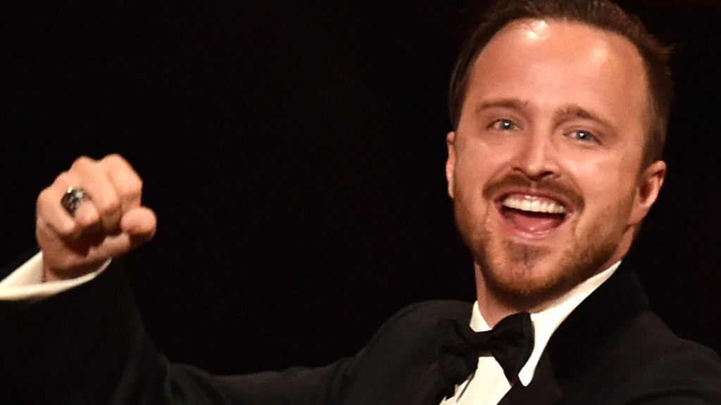 Aaron Paul punches the air while accepting the best supporting actor award at the Emmys.