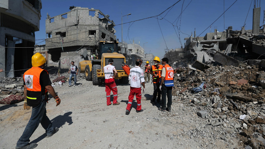 Palestinian rescue workers search for the dead and wounded during a two-hour truce. (AAP)