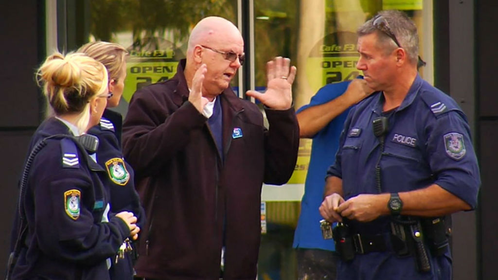 Police speak to the victim of an alleged carjacking in Sydney this morning.