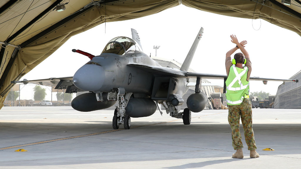 A Royal Australian Air Force (RAAF) airman waits to marshal a F/A-18F Super Hornet from the Australian Defence Force Air Task Group in the Middle East. Prime Minister Tony Abbott has announced Australian aircraft will begin flying over Iraq from today. (AAP)