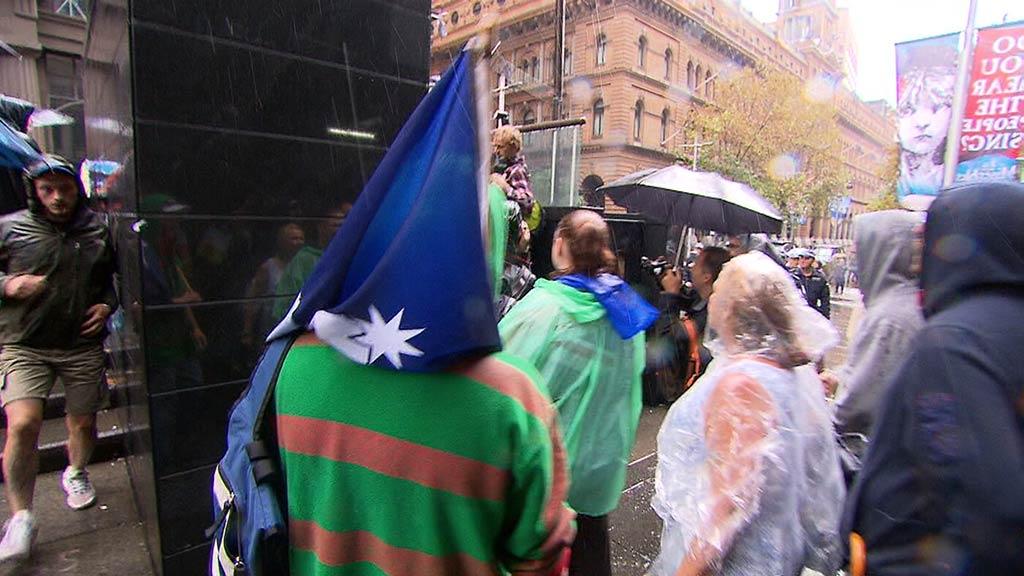 A man drapes an Australian flag over his head at the Sydney rally. (9NEWS)
