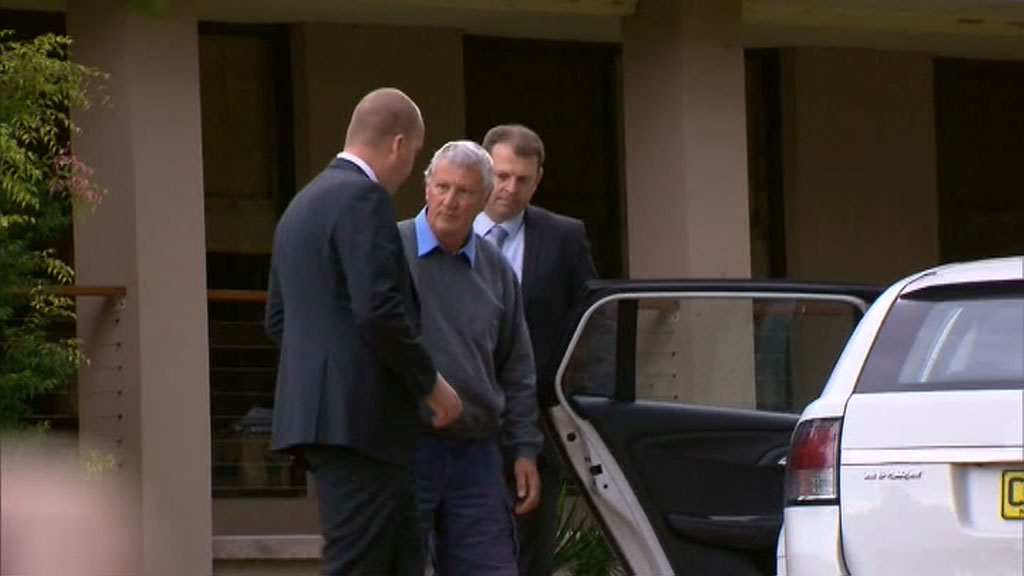 Homicide detectives lead Mr Spedding to their car outside his Bonny Hills home. (9NEWS)