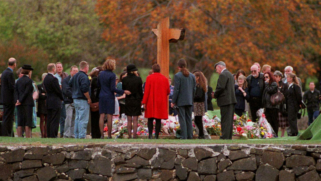 Families and friends gather around the memorial at Port Arthur for a minute's silence at a service in memory of the 35 people killed, on the first anniversary in 1997. (AAP)