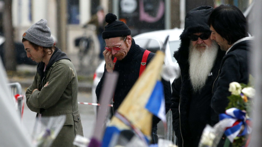 Eagles of Death Metal members Julian Dorio, Jesse Hughes, Dave Catching and Matt McJunkins pay their respects. (AAP)