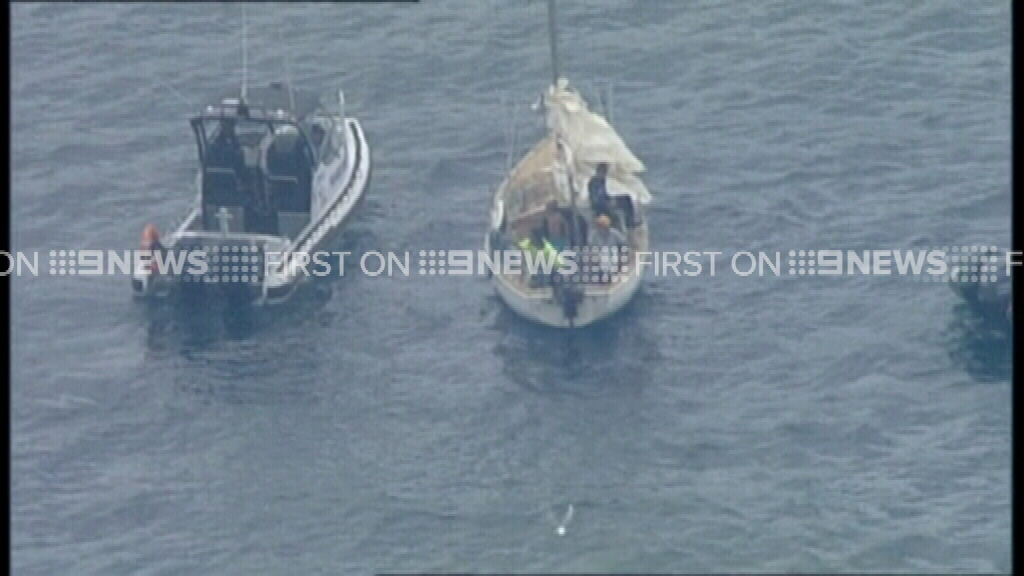 The police launch pulls alongside the craft. (9NEWS)