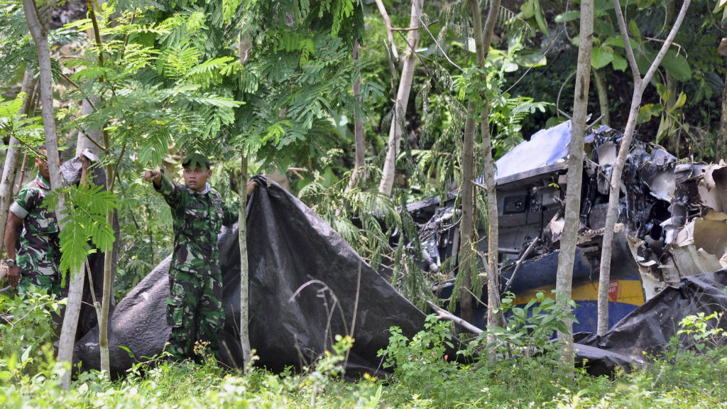 Indonesian soldiers try to cover the wreckage of an Indonesian Air Force's T-50 Golden Eagle. (AAP)
