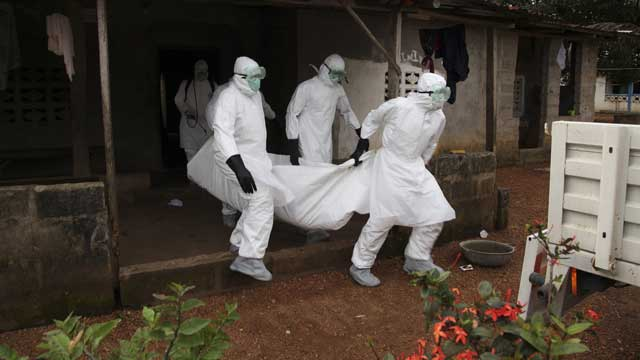 Liberian nurses carry the body of an Ebola victim from a house during an outbreak in 2015. Source: AAP.