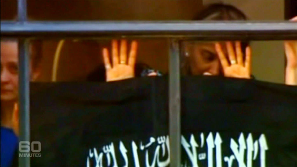 Several of the hostages were forced to hold an Islamic flag against the glass. (9NEWS)