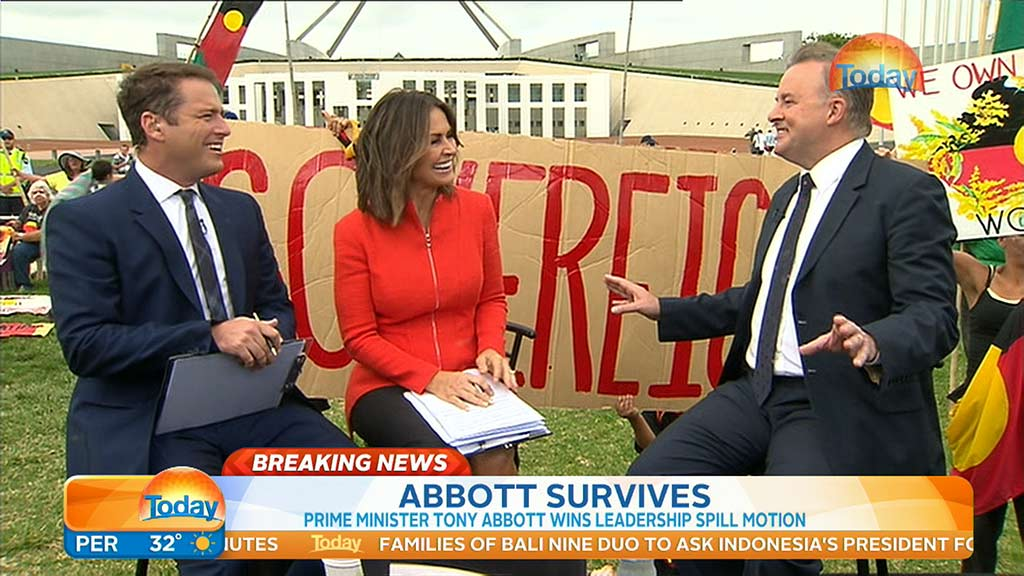 Karl Stefanovic and Lisa Wilkinson share a laugh with Labor MP Anthony Albanese as protesters assemble in the background. (9NEWS)