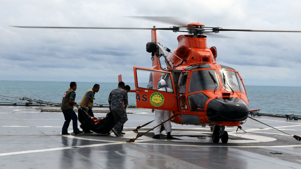 Indonesian Navy crew carry the body of a victim of crashed AirAsia flight QZ8501. (AAP)