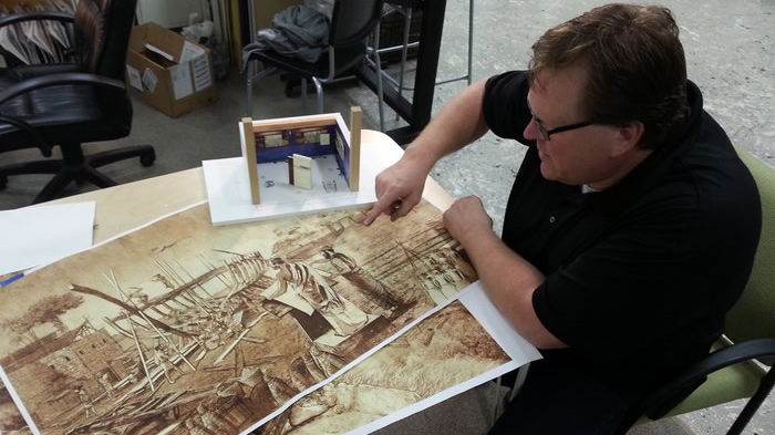 A member of the Ark Encounter design team shows plans for a Biblical scene set to feature as a theme park exhibit. (Ark Encounter)