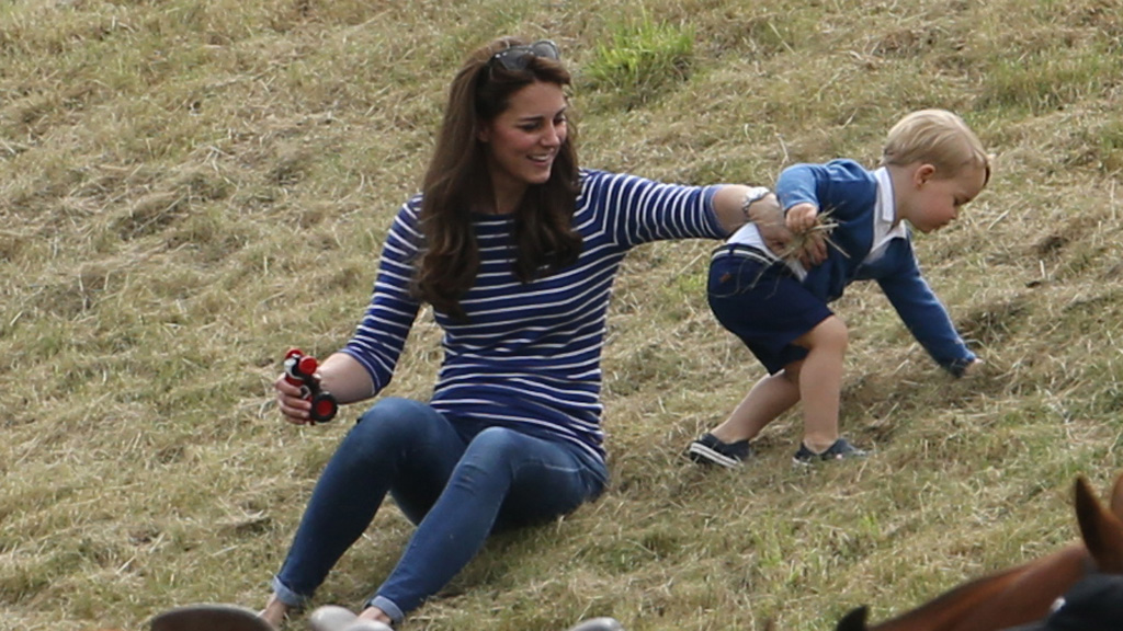 The young prince playfully rolled around next to his smiling and laughing mother. (AAP)