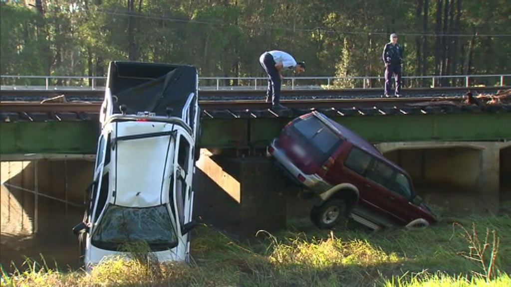 Four people died after these two cars were washed from the road in Caboolture yesterday. (9NEWS)