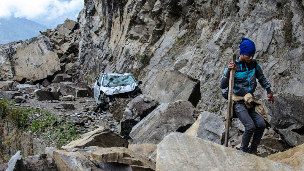 A Nepalese man walks over fallen rocks and past a crushed car on the way to Dhunche. (AAP)