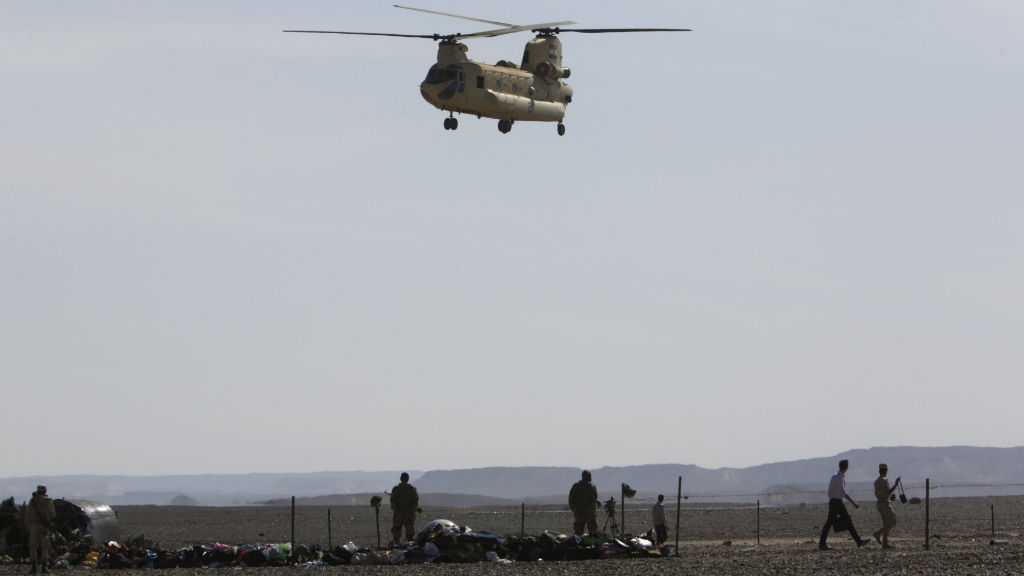 An Egyptian military helicopter lands near the wreckage of a passenger jet. (AAP)