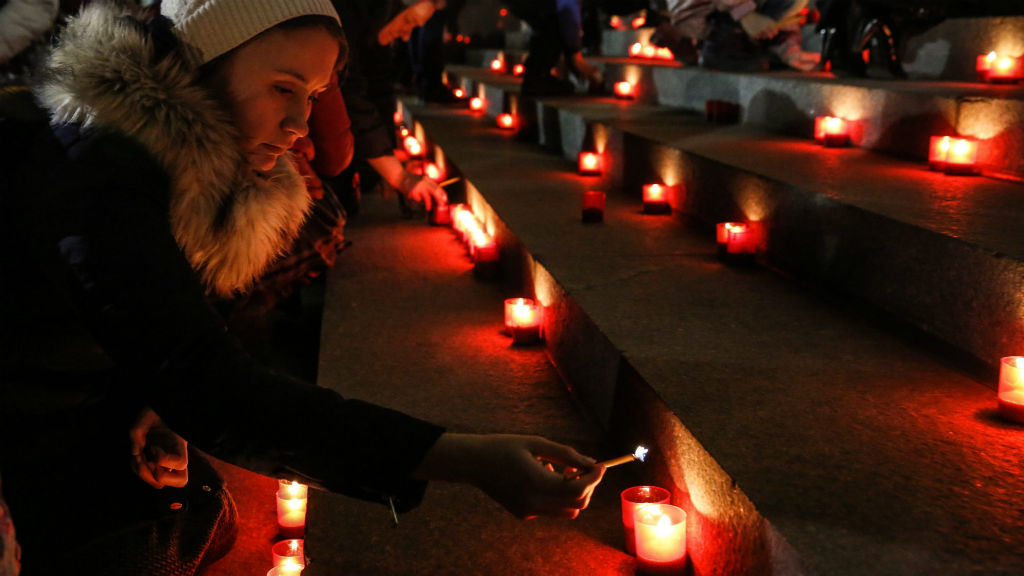 Mourners light candles to the memory of victims of the disaster in Moscow. (AAP)