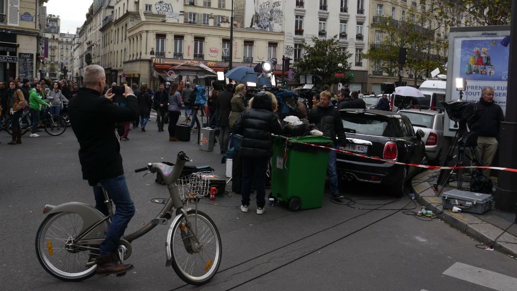 A man on a hire bicycle stops to take a photo of the media contingent on Boulevard Voltaire.