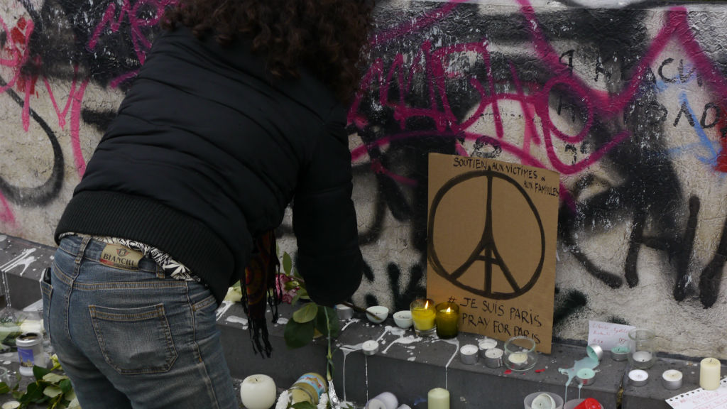 A woman lights a candle near a Parisian peace sign at Place de la Republique. (9NEWS)