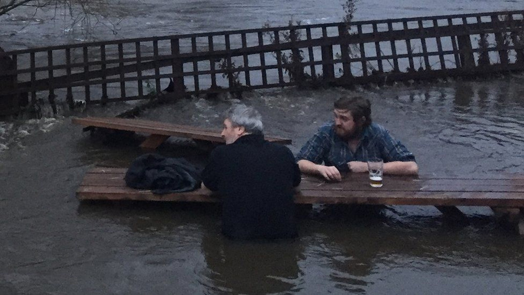 Two UK men decide to grab a pint as beer garden floods around them