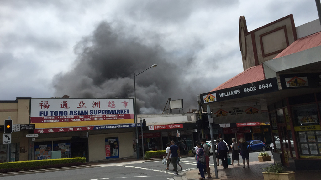 The fire has spread to the shared roof space of three other businesses. (9NEWS)