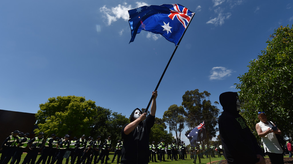 Four people have been arrested in Melton today during a heated clash between anti-racism and Reclaim Australia protesters.<br /><br />An anti-Islamic Reclaim Australia protester waves an Australian flag during protests in Melton today. (AAP)<br /><br /><b>Click through the gallery to see more photos from today's protests.</b>