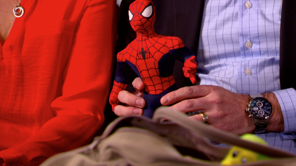 William's parents hold his Spider-man toy. (9NEWS)