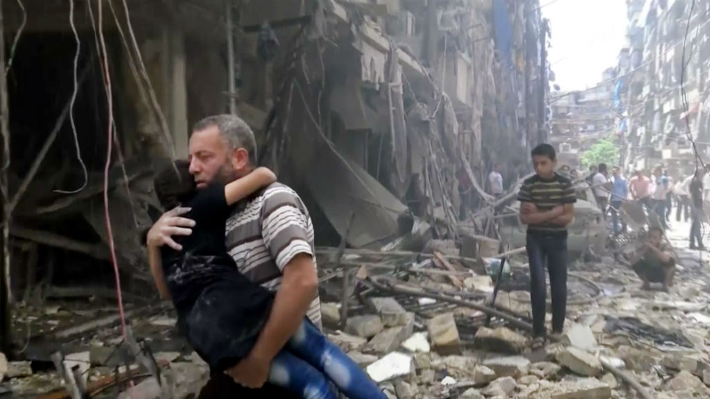 A man carries a child after airstrikes hit the Syrian city of Aleppo. (AAP)