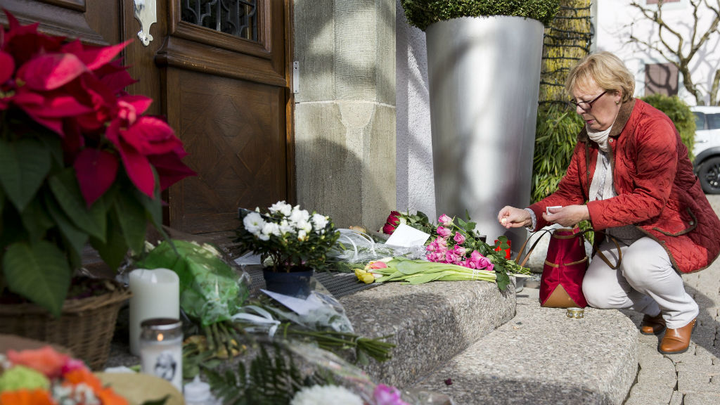 A mourner lays tributes outside the restaurant Hotel de Ville in Crissier, Switzerland.