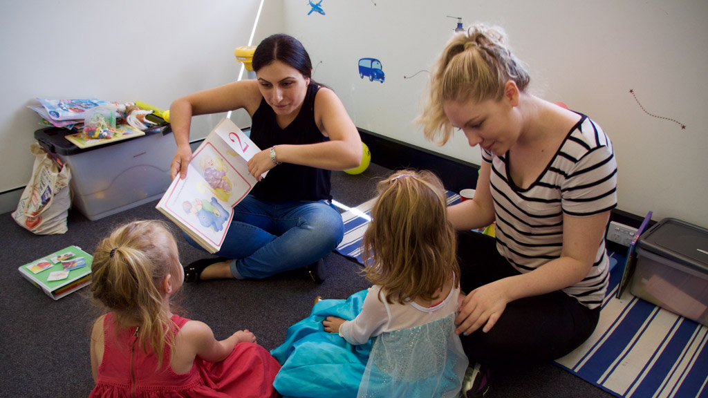 The therapists tell twins Dearne and Marissa a story. (Ehsan Knopf/9NEWS)