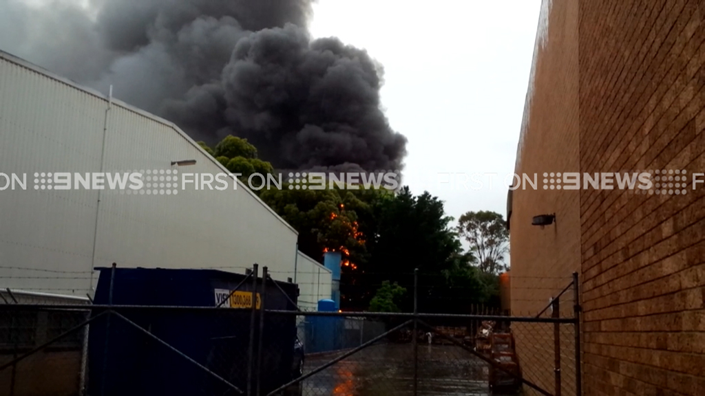 Thick smoke gushes from the building. (9NEWS)