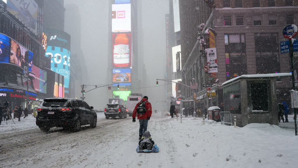 David Suker pulls his son Tadhg Suker during heavy snowfall in New York's Times Square. (AAP)