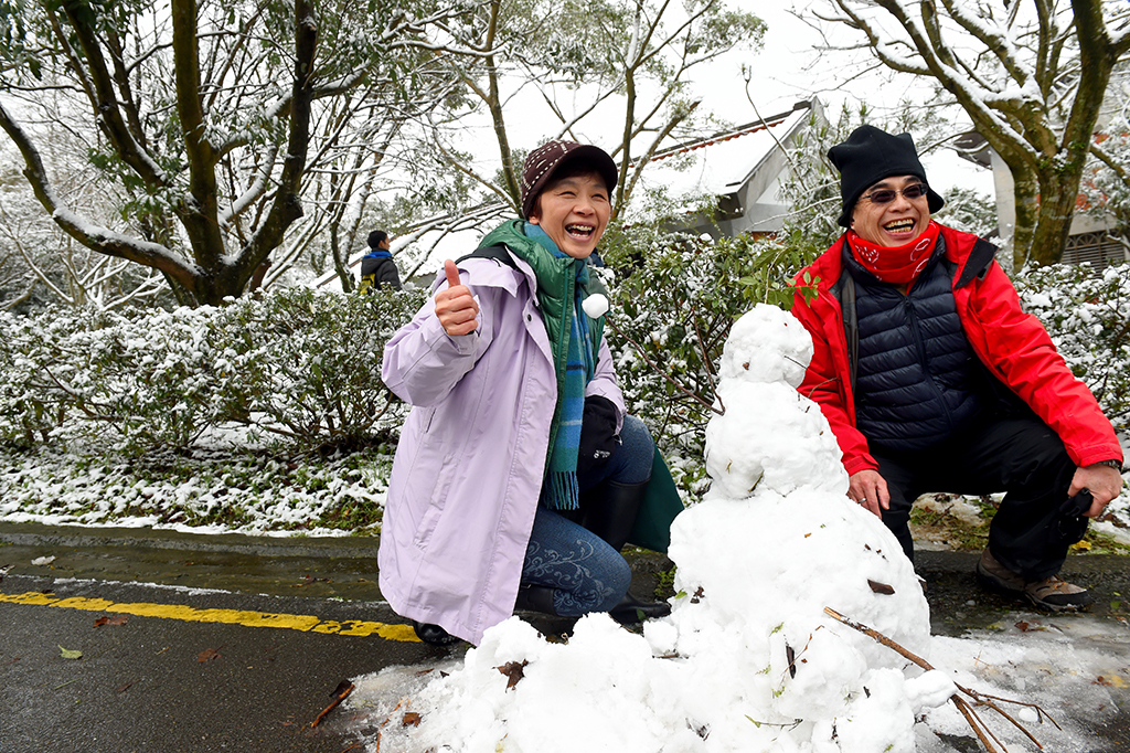 Tourists enjoy the snow at Yangming Mountain in Taipei