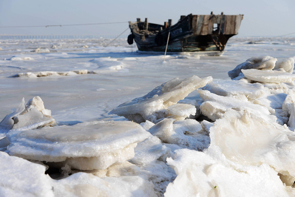 A fishing boat lies on the frozen sea of Jiaozhou Bay in Qingdao City, east China's Shandong Province