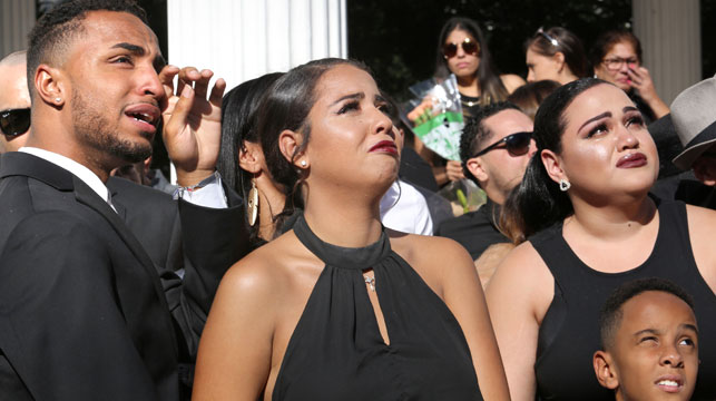 Isaiah Henderson, Tatiana Harris and Khiana Marshall watch 49 white balloons after they were released during the funeral for their mother. (AAP)