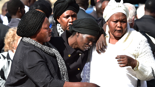 Akon Guode (centre), the mother of three children killed in a lake in Wyndham Vale, makes her way from a funeral service in April, 2015. Source: AAP