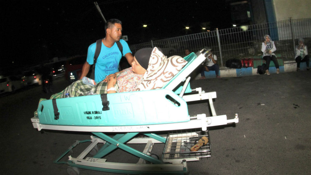 A man pushes a relative who lies on a hospital bed as they were told to get to higher ground in Pedang.