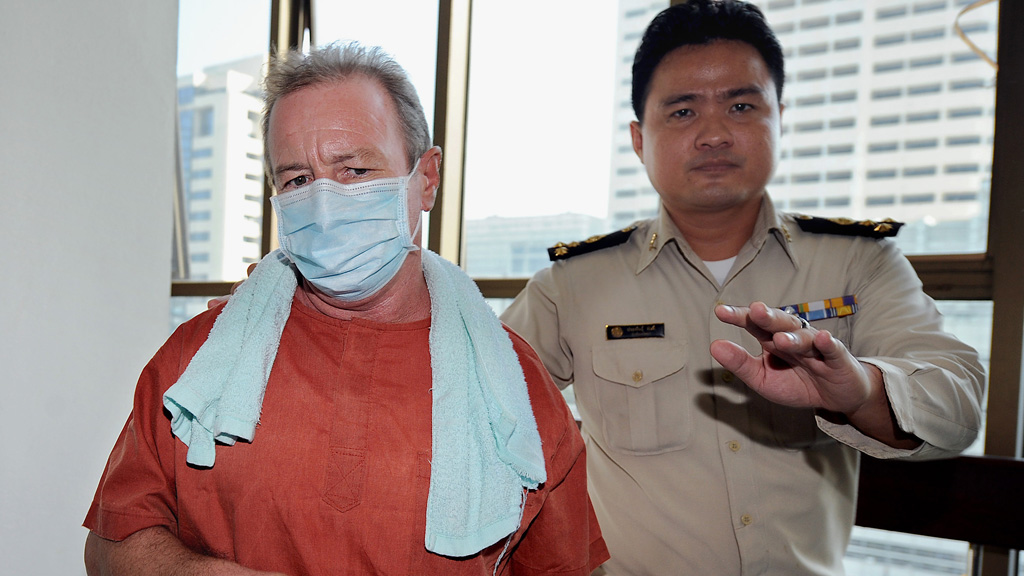 Kinch escorted by a Thai court official as he arrives at the crime court in Bangkok on November 27, 2009. (AFP)