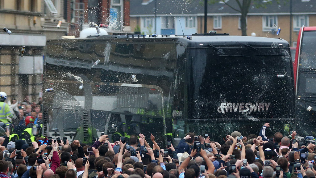 Fans congregate in the street and throw bottles and cans at the Manchester United team bus prior to the match. (Getty)