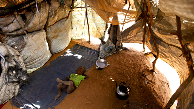 A Somali baby boy sleeps in a makeshift shelter on the outskirts of Dadaab, 2011. Source: AAP