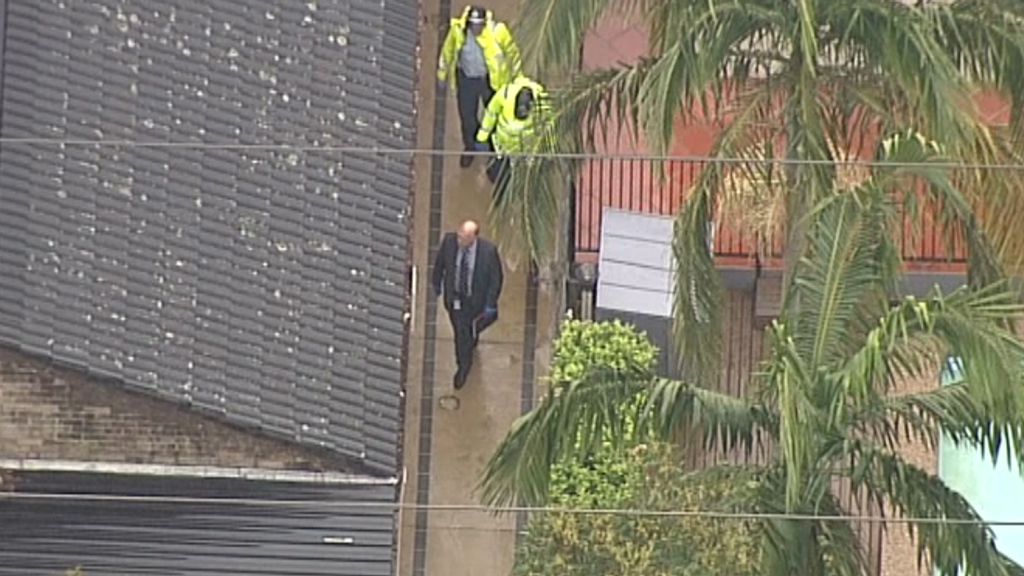 Investigators walk down a side path along the home on Sir Thomas Mitchell Drive. Source: 9News