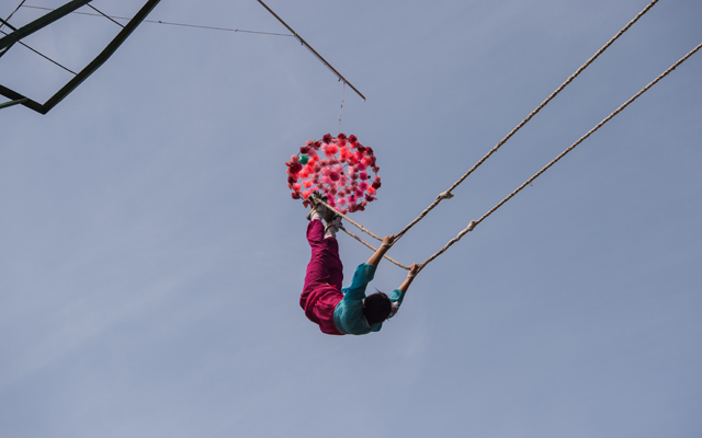 To succeed in the swing event the athlete must touch the flowers hanging high above the ground. Source: KIM WON-JIN / AFP