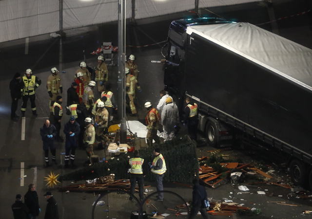 Authorites inspect the scene after a truck sped into a Christmas market in Berlin, killing at least 12 people and injuring dozens more.