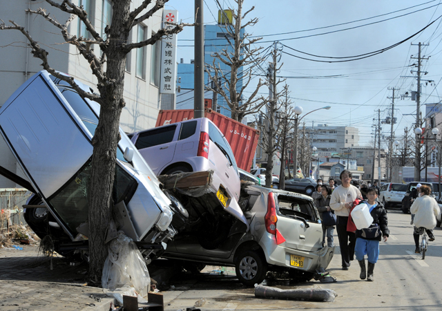 The 2011 earthquake and tsunami: Local residents walk past cars damaged in the tsunami on a street in Tagajo on March 13, 2011 - two days after a massive 8.9 magnitude earthquake hit the region.