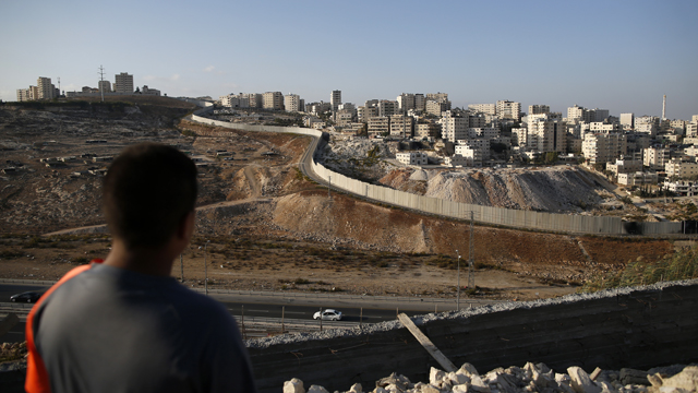 A picture taken on October 18, 2016 from the east Jerusalem Arab neighbourhood of Issawiya shows a Palestinian youth looking on as the Palestinian Shuafat refugee camp (R) is seen behind the controversial Israeli separation wall.